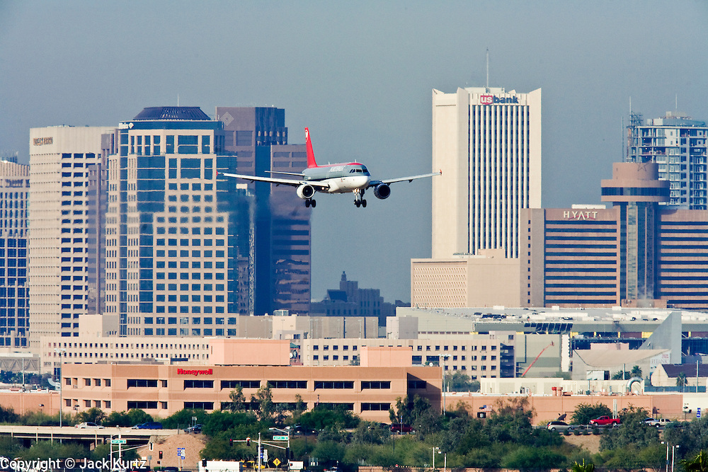 06 DECEMBER 2007 -- PHOENIX, AZ: A Northwest Airlines plane comes in for a landing at Sky Harbor Airport. Sky Harbor International Airport is on the edge of downtown Phoenix, in the middle of the Phoenix metropolitan area. It is one of the largest airports in the country with more than 1,400 flights daily. The airport's proximity to downtown though, less than five miles from the city center, is both a blessing and a curse. It takes about 15 minutes to get to the airport from downtown, but a proposed 510 foot tall building proposed in downtown, near the airport flight path, has raised safety concerns. The Federal Aviation Administration wants the development capped at 355 feet. Similar concerns about a proposed football stadium in Tempe, which borders the east side of the airport, scuttled that project and led to the stadium being built in Glendale, about 30 miles from the airport.  PHOTO BY JACK KURTZ