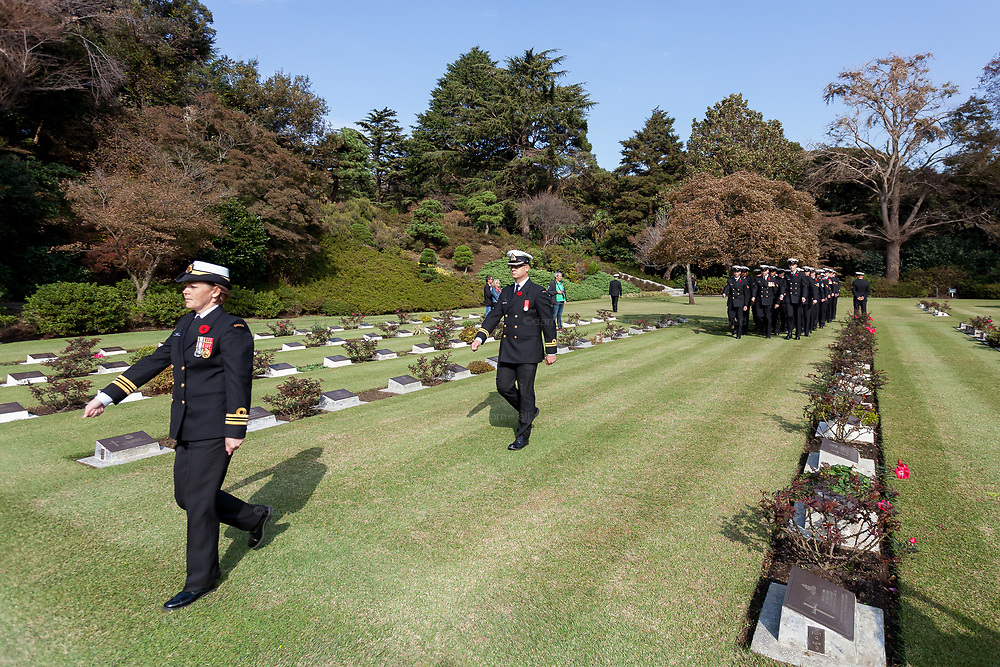 A Canadian female sailor leads naval personnel as they march during the Remembrance Sunday ceremony at the Hodogaya, Commonwealth War Graves Cemetery in Hodogaya, Yokohama, Kanagawa, Japan. Sunday November 11th 2018. The Hodagaya Cemetery holds the remains of more than 1500 servicemen and women, from the Commonwealth but also from Holland and the United States, who died as prisoners of war or during the Allied occupation of Japan. Each year officials from the British and Commonwealth embassies, the British Legion and the British Chamber of Commerce honour the dead at a ceremony in this beautiful cemetery. The year 2018 marks the centenary of the end of the First World War in 1918.