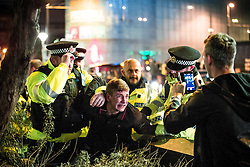 © Licensed to London News Pictures . 01/01/2016 . Manchester , UK . Police detain a man in handcuffs . Revellers in Manchester on a New Year night out at the clubs around the city centre's Printworks venue . Photo credit : Joel Goodman/LNP