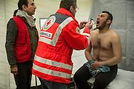 Nea Kavala, Greece - 23.03.2016  <br /> <br /> Dr. Bernhard Roemhild examined Khalil Bako, from the Syrian city Afrin, in the German Red Cross health center inside refugee camp Nea Kavala. He is assisted by an interpreter. An international team of the Red Cross assumes the camp on his work. Is coordinating the work of the German and the Finnish Red Cross.3,515 refugees are currently living in the official Greek refugee camp in Nea Kavala. The Greek military opened the 600 tents big camp about 1 month ago. The conditions in the camp are meager : In case of rain the area is partially submerged also the tents are not heated .<br /> <br /> Dr. Bernhard Roemhild untersucht Khalil Bako, aus dem syrischen Afrin, in der DRK Gesundheitsstation im Nea Kavala Flüchtlingscamp. Er wird dabei von einem Uebersetzer unterstuetzt Ein internationales Team des Roten Kreuzes nimmt im Camp seine Arbeit auf. Koordiniert wird die Arbeit vom deutschen und dem finnischen Roten Kreuz. 3.515 Fluechtlinge leben derzeit in dem offiziellen griechischen Fluechtlingscamp in Nea Kavala. Das griechische Militaer eröffnete das aus 600 Zelten bestehende Lager etwa 1 Monat vorher. Die Bedingungen im Lager sind dürftig: Bei Regen steht das Gelaende teilweise unter Wasser außerdem sind die Zelte nicht geheizt.