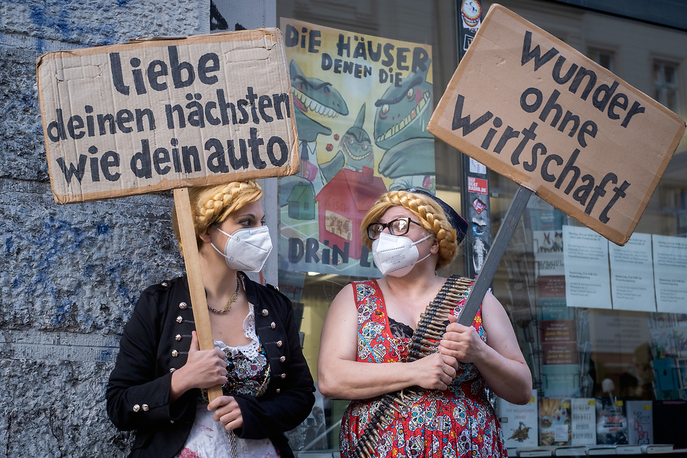 """Proteste gegen Verdrängung des Buchladens Kisch & Co in der Oranienburger Straße 25 in Berlin Kreuzberg, zwei Tage vor dem Gerichtstermin im Räumungsprozess. Der Mietvertrag des Buchladens ist Ende Mai 2020 ausgelaufen. Laut Aussagen der Mieter haben die Vermieter dem Buchladen ein Angebot gemacht, den Mietvertrag bis Ende des Jahres zu verlängern, wenn die Mieter sich verpflichten, dann die Räume zu verlassen und sich in verschiedenen Medien positiv über den Vermieter zu äußern. Anderen Gewerbemietern des Hauses wurden Mietsteigerungen von 13 € auf 38 €/qm angekündigt. Demonstrantinnen mit Schildern """"liebe deinen nächsten wie dein auto"""" und """"wunder ohne wirtschaft"""". Berlin, Deutschland, 20.04.2021.<br /> <br /> [© Christian Mang - Veroeffentlichung nur gg. Honorar (zzgl. MwSt.), Urhebervermerk und Beleg. Nur für redaktionelle Nutzung - Publication only with licence fee payment, copyright notice and voucher copy. For editorial use only - No model release. No property release. Kontakt: mail@christianmang.com.]"""