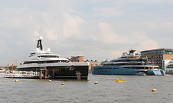 © Licensed to London News Pictures. 04/07/2018. London, UK.  The new 243 feet long superyacht, Elandess arrives in London for the first time ever on the River Thames and moors  at HMS President, the Royal Navy Reserve Unit and seen here this evening opposite the Aviva superyacht which arrived last week. Elandess was built at the Abeking and Rasmussen shipyard in Germany, launched in May 2018 and has just completed sea trials ahead of its London visit. Elandess has an axe-bow, dark hull and low-slung superstructure. There are a variety of entertaining communal spaces, from the 8 x 2.5-metre superyacht swimming poollocated on the massive sun deckto the Nemo Loungewith portholesbelow the waterline and an observation lounge on the upper deck. Guest accommodation includes six staterooms, including the master suitewhich is placed forward on the main deck with an observation lounge directly above on the upper deck.  Photo credit: Vickie Flores/LNP