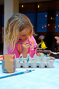 Young blond girl of 4 engrossed in painting handwork made from scraps