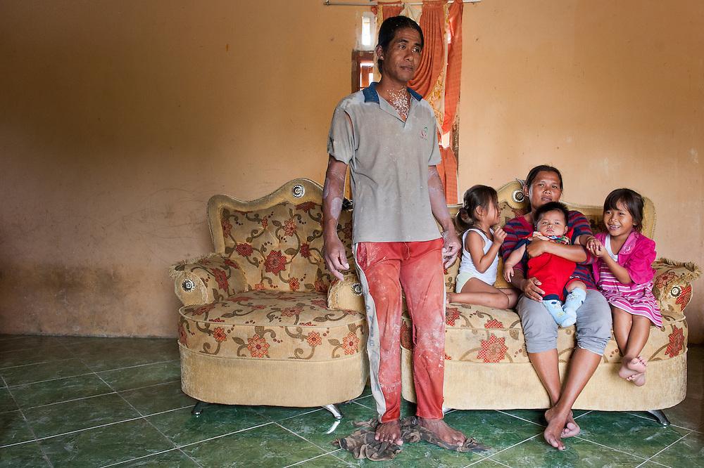 Purnomo (40 years) with his wife Elia (33 years) and his children  Pepi (5 years), Eric (4 month) and Bening (7 years). They live in a house with sight on their own illegal tin mine, the only source of income for this family in Mapur.<br /> Bangka Island (Indonesia) is devastated by illegal tin mines. The demand for tin has increased due to its use in smart phones and tablets.<br /> <br /> <br /> <br /> Purnomo (40 ans) avec sa femme Elia (33 ans) et ses enfants Pepi (5 ans), Eric (4 mois) et Bening (7 ans). Habitent une maison dans une mine. <br /> Mine d'étain illégale et familiale dans jardin à <br /> Mapur. <br /> L'île de Bangka (Indonésie) est dévastée par des mines d'étain sauvages. la demande de l'étain a explosé à cause de son utilisation dans les smartphones et tablettes