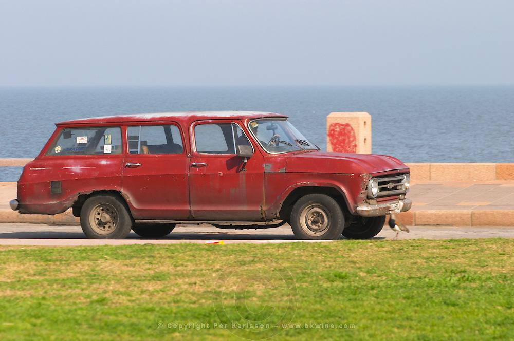 An old Chevrolet car in rusty red., on the riverside seaside walk along the river Rio de la Plata Ramblas Sur, Gran Bretagna and Republica Argentina Montevideo, Uruguay, South America
