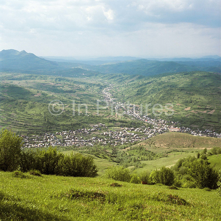 A view of the village of Botiza and surrounding agricultural landscape, Maramures, Romania. In the Romanian Carpathians, the agricultural landscape consists of a diverse mixture of small fields, meadows and orchards situated around villages, interspersed with forest and woodlands.