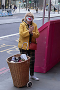 As Londoners await the second coronavirus national lockdown, a woman wearing a cheerful smile face mask in the City of London a few days before a month-long total lockdown in the UK on 2nd November 2020 in London, United Kingdom. The three tier system in the UK has not worked sufficiently, to suppress the virus, and there have have been calls by politicians for a 'circuit breaker' complete lockdown to be announced to help the growing spread of the Covid-19.