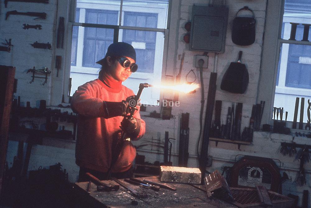 A woman welder operating a blowtorch