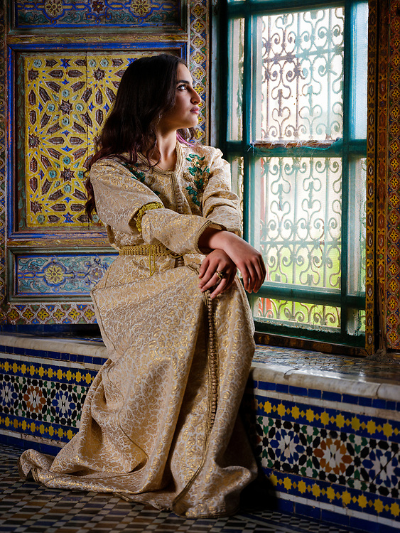 FEZ, MOROCCO - CIRCA MAY 2018:  Young Moroccan woman in traditional dress seating by a window in Fez