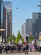 A news helicopter repeatedily flies over the crowd and the Chicago River as members of the Chicago Police Department watch over a demonstration of anti-Sharia law protesters