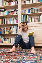 Senior woman sitting on the floor in front of bookshelf and reading, Munich, Bavaria, Germany