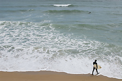 Surfer in a wetsuit walking with his surfboard into the ocean