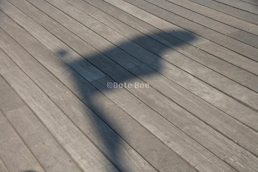 shadow of a flag on a wooden floor board walk