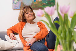 Senior woman day dreaming while sitting on sofa, Munich, Bavaria, Germany