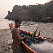 Fisherman cleans his net at sunset.