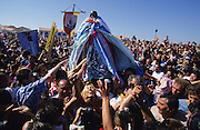 The procession of Saint Sara arrives at the seashore, surrounded by thousands of Roma, Gypsy, Gitan and Manouche pligrims, and flanked by Traditional Camargaise Guardians and their horses. <br /><br />Europe, France, Camargue, Saintes Maries de la Mer. Saint Sara, the patron saint of the gitans. Gypsies come from all over Europe to pay hommage to her during the 'pelerinage des gitans' the gypsy pilgrimmage. They camp around the seaside town for 2 weeks of the year, where they are tolerated by the locals. The carry Saint Sara and the Saintes Maries from the church to the seashore in two cermonies on the 24th and 25th of May every year.