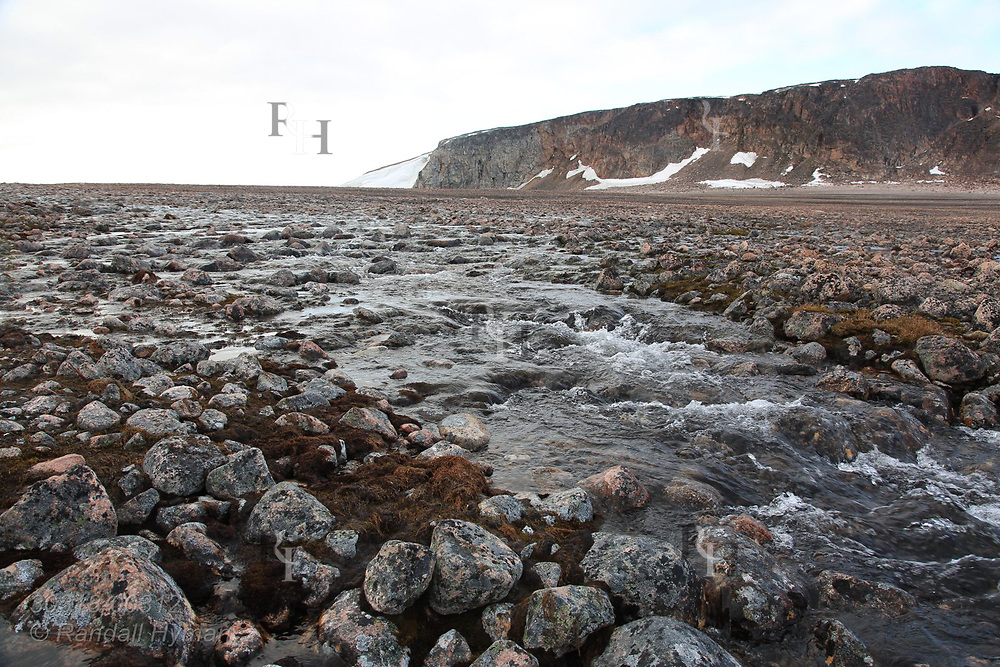 Glacial meltwaters rush across rocky shore of Rijpfjorden on Nordaustlandet in late July; Svalbard, Norway.