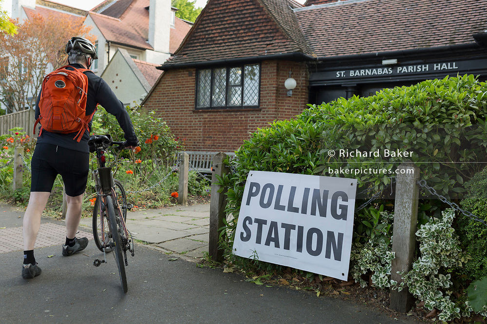 Before voting for the European Elections commences at 7AM, a cyclist enters the Polling Station at St. Barnabas Parish Hall in Dulwich Village, on 23rd May 2019, in south London, England UK.