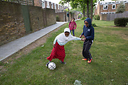 Young boys and girls play football at Cressingham Gardens estate on 11th May 2017 in South London, United Kingdom. Cressingham Gardens is a council garden estate in Lambeth. Located on the southern edge of Brockwell Park, it comprises of 306 dwellings. It was designed at the end of the 1960s by the Lambeth Borough Council architect Edward Hollamby, and built at the start of the 1970s. In 2012 Lambeth Council proposed regeneration of the whole estate, a decision highly opposed by many residents and a campaign to stop the redevelopment has been in place since.