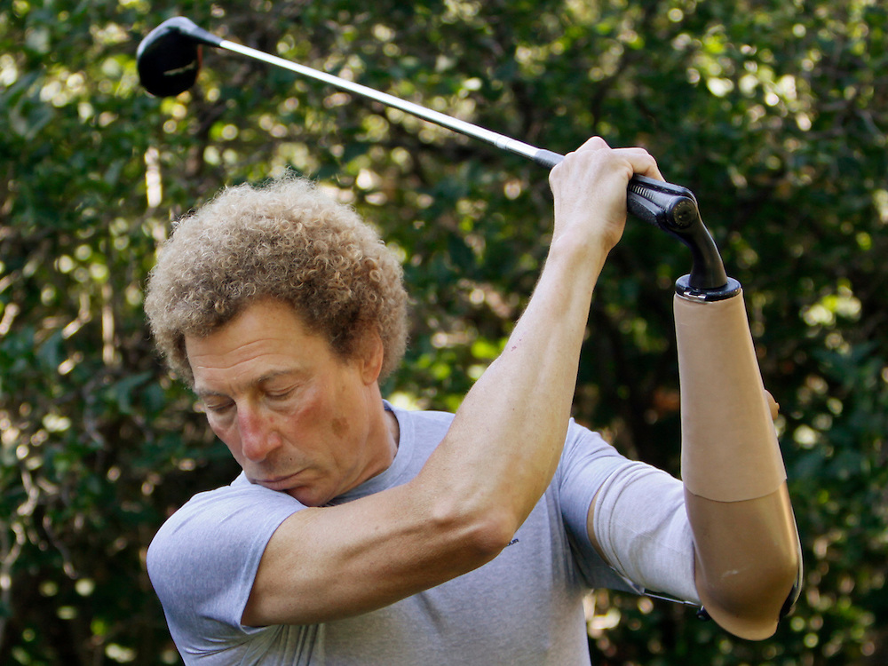 Bob Radocy of TRS Inc. swings a golf club with a golf hand replacement at his home in Boulder, Colorado August 20, 2009. Radocy designs and builds prosthetic attachments that allow amputee athletes to participate in multiple sports. The golf hand stores energy on the backswing improving power through the downstroke. REUTERS/Rick Wilking (UNITED STATES)