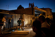 Workers remove the body of a man who died by gun shots at Itinga neighborhood in Salvador, Brazil, Wednesday Feb.  8, 2012. <br /> <br /> About one-third of Bahia's 30,000 police went on strike a week ago and murders in the capital's metropolitan area immediately spiked, reaching double normal rates before 2,000 troops were sent in Sunday to patrol the city in armored personnel carriers. The striking police officers are demanding pay raises and amnesty for what a judge ruled an illegal work stoppage.