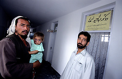 KABUL 04 August 2005..KHAIR-KHANA PRIVATE CLINIC....Janat Gul - Shabana's father - craddles her daughter on his harms while meeting Dr Ahnadi's assistant...Dr. Waheed Ahmadi, who works at Jamhoriat Hospital and also run is private studio, will refers Shabana to a Dermatologist...