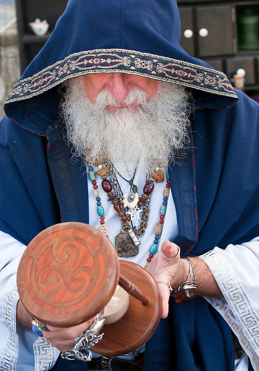 Old man, fortune teller looking at hour glass.