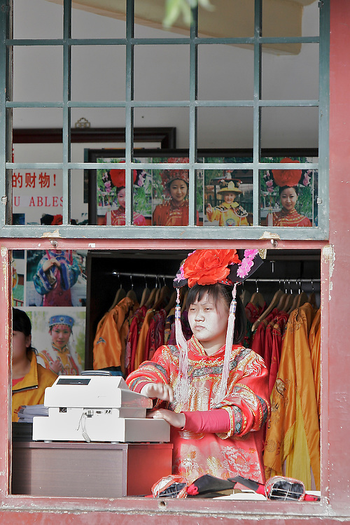 A worker at the Summer Palace waits for customers. The Summer Palace in north west Beijing, China was built in the Jin Dynasty.  The Summer Palace is over 700 acres, 3/4 of which is the Kunming Lake.
