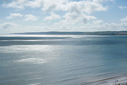 Sunlight reflects off the blue sea of Filey Bay viewd from the Cliff top just above Coble Landing looking towards Flambrough Head