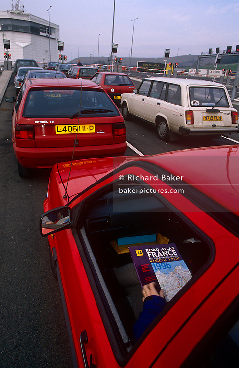 A British passenger has a road map for the year 1996 on their lap in the left-hand seat as they queue with other Brits at the Eurotunnel terminal at Folkestone, England. Their journey will take them across the English Channel to   France via the Channel Tunnel.