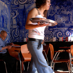 Guimaraes, Portugal - An older man sits in a cafe off of the Plaza Oliviera, home to a church and pousada of the same name.  Typically, bright blue tiles adorn the walls...Photo by Susana Raab