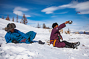 Tsaatan reindeer herders making a wine offering to their gods while taking a rest break from walking their reindeer (Rangifer tarandus) in deep snow in the mountains, Khovsgol Province, Mongolia