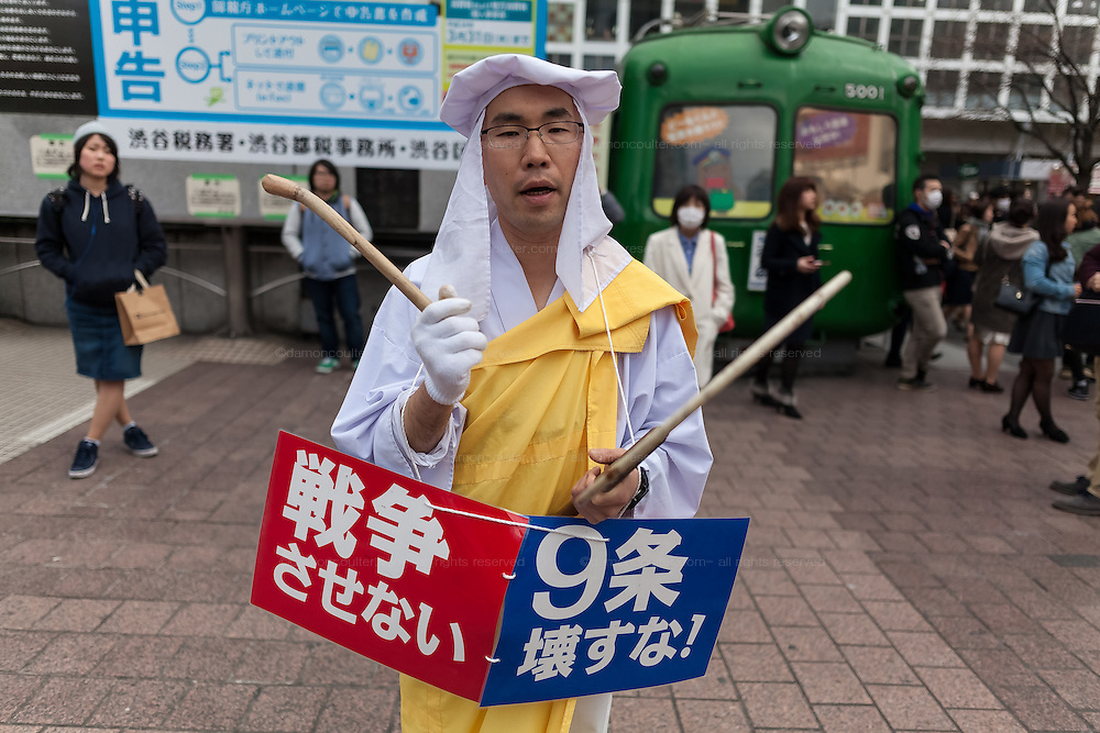 A lone Buddhist Monk protests the reinterpretation of Japan's pacifist constitution Article 9. Shibuya, Hachiko Square, Tokyo, Japan. Friday March 25th 2016. The Prime Minister, Shinzo Abe has changed the constitution to allow collective self defence, meaning Japanese military forces can take part in wars with allies for the first time since WW2.