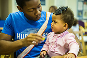 A young father feeding apple to his baby daughter during a family visit in HMP Brixton, South London on the 26th of July 2016, London United Kingdom. The Prisoner Advice & Care Trust (PACT) organise special family days that help the men inside the prison connect with and support their partners and children on the outside. (photo by Andy Aitchison)