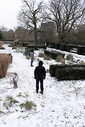 Two men stand at different angles in a snowy landscape at Ruskin Park in south London, SE24, on 8th February 2021, in London, England.