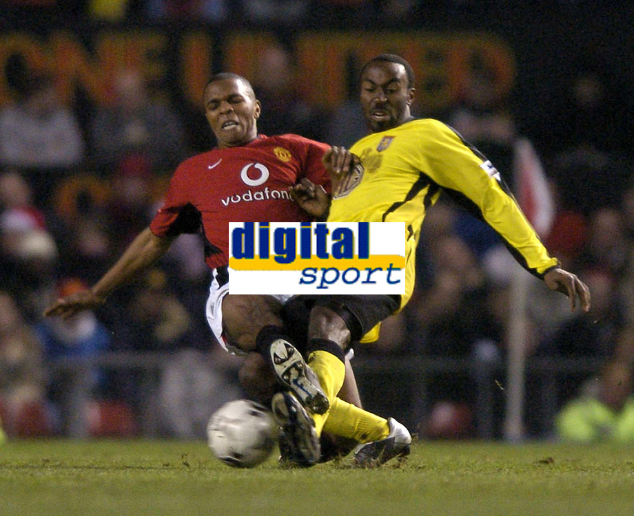 Photo: Richard Lane.<br />Manchester United v Aston Villa. Barclaycard Premiership. 06/12/2003.<br />Quinton Fortune and Darius Vassell challenge for the ball.