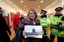 © under license to London News Pictures. 18/12/2010: Approximately 25 protesters picketed Top Shop and other shops associated with Philip Green, Vodafone and Boots to highlight corporate tax-avoidance. Outside Vodafone on Manchester's Market Street police stand ready. The protest was peaceful