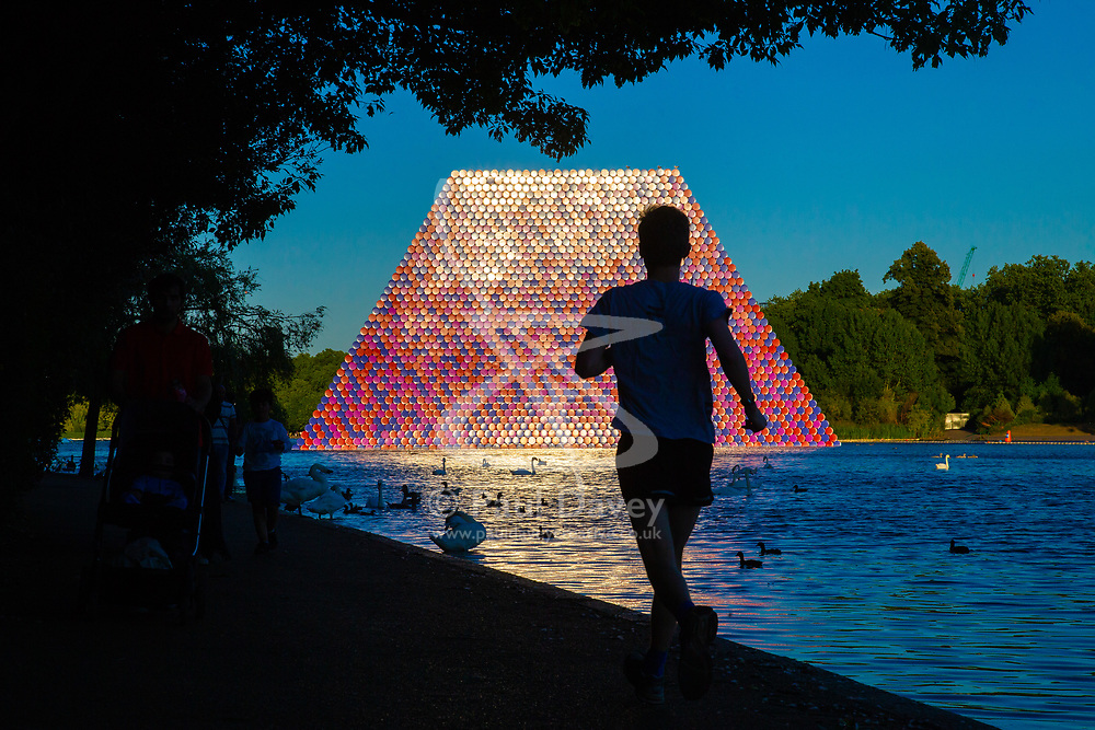 A runner is cast into silhouette against the light reflected off the setting sun on artist Christo's Mastaba, an installation made up of over 7,000 barrels floating on The Serpentine in London's Hyde Pak. London, July 02 2018.
