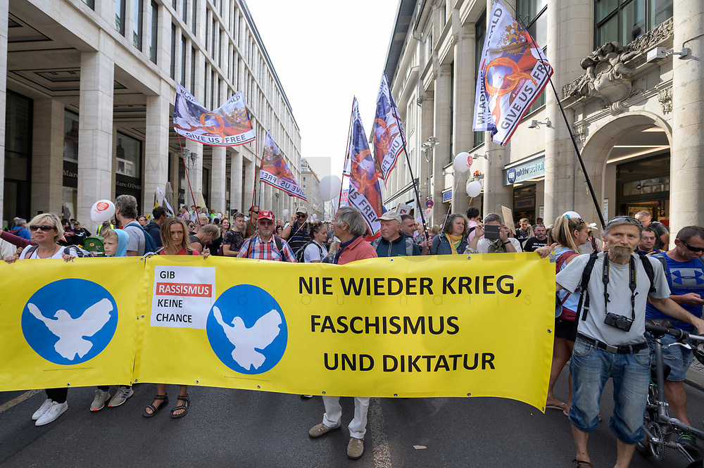 """29 AUG 2020, BERLIN/GERMANY:<br /> Demonstanten mit Transparten """"Nie wieder Krieg, Faschismus und Diktstur"""" dahinter Demonstranten mit QAnon-Flaggen, Demonstration gegen die Einschraenkungen in der Corona-Pandemie durch die Initiative """"Querdenken 711"""" aus Stuttgart unter dem Motto """"invites Europa - Fest für Freiheit und Frieden"""", Friedrichstrasse<br /> IMAGE: 20200829-01-017<br /> KEYWORDS: Demo, Protest, Demosntranten, Protester, COVID-19, Corona-Demo"""