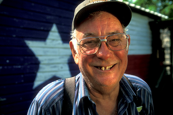 Portrait of Elderly Country Store Proprietor Wearing Hat and Suspenders Standing in Front of Building Painted With Texas Flag