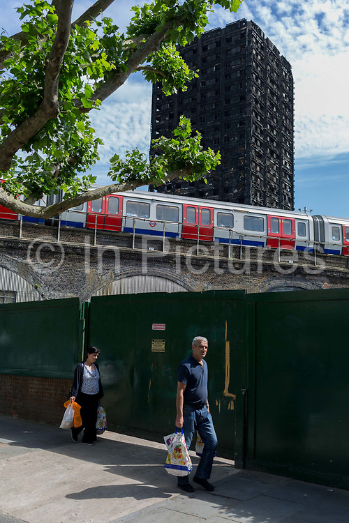 Twelve days after the devastating fire that killed an unspecified number of people in Grenfell Tower, local people carry their shopping past the charred and blackened tower block which remains a crime scene, on 26th June 2017, in the London borough of Kensington & Chelsea, England.