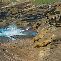 Tourists watch as Pacific Ocean waves crash onto eroded sandstone cliffs on the southeast shore of Oahu, Hawaii.
