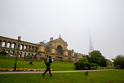© Licensed to London News Pictures. 29/04/2019. London, UK. A man walking his dog in Alexandra Palace park as mist envelopes the transmission tower (one of the oldest television transmission sites in the world) above Alexandra Palace. Photo credit: Dinendra Haria/LNP