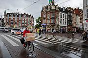 Een vrouw fietst met een doos van de Bijenkorf over het Muntplein in Amsterdam.<br /> <br /> A woman cycles with a box at the Munt Square in Amsterdam.