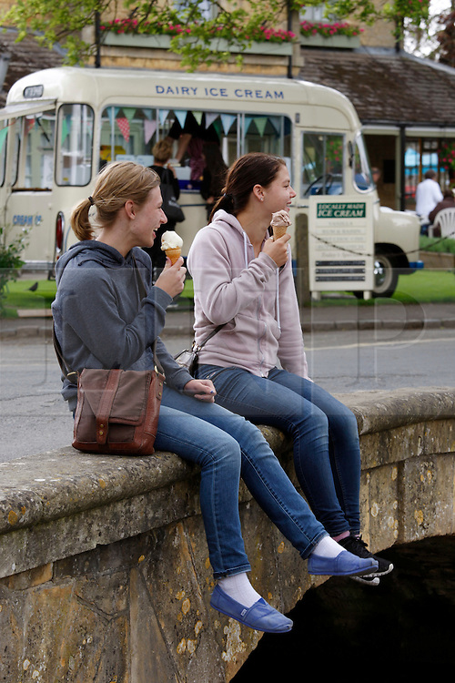 © Licensed to London News Pictures.14/06/2012. Bourton-0n-the-Water, UK. Summers here, tourists flock to the Costswolds to enjoy a British summer. Pictured, two young girls visiting from Oregon in the U.S.A, take a rest on one of the bridges that straddle the picturesque village  of Bourton-on-the-Water.Photo credit : Dave Warren/LNP