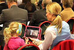 Mother keeping daughter amused in the audience at the AGM of Mysight, a charity for people with visual impairments.