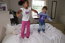 Two young girls playing and jumping on the bed,