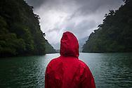 Figure wearing a red jacket looks across Ba Be lake in Bac Kan Province, Vietnam, Southeast Asia