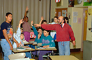 Teacher and Spanish language students with hands up age 50 and 14.  Golden Valley Minnesota USA
