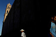 Men walk late afternoon next to the Cathedral in Ciudad Juarez, Mexico,  April 9, 2009. (AP Photo/Rodrigo Abd)